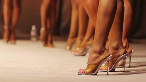 Fit legs of beautiful female fitness models posing on stage in high heel shoes Live Action