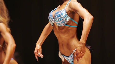Slim ladies demonstrating perfect fit bodies in front and side poses at contest Live Action