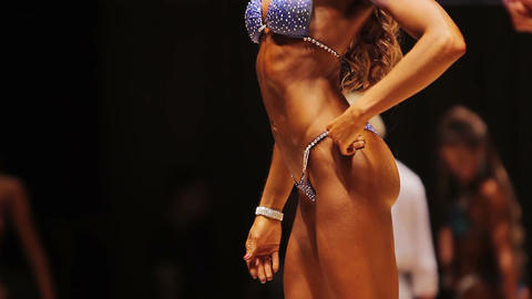 Perfect athletic body of professional female fitness model posing at competition Footage