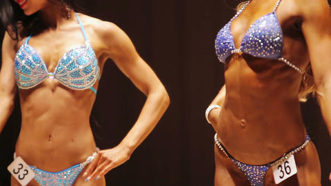 Athletic women demonstrating perfect fit bodies at fitness bikini competition Footage