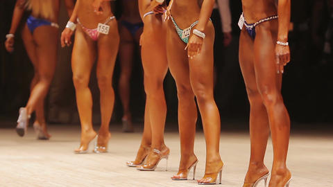 Women with beautiful tanned fit bodies walking on stage, fitness competition Live Action