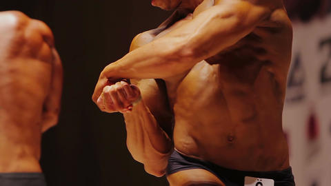 Strong man standing in side chest pose at bodybuilding contest, muscular body Footage
