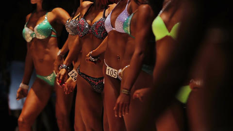 Attractive ladies in bikini lined up on stage at beauty contest, feminine bodies Live Action