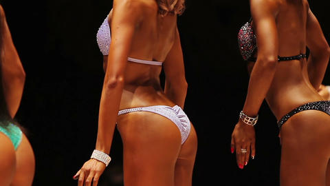 Fitness models standing on stage in rear pose, showing ideal fit back and bottom Live Action