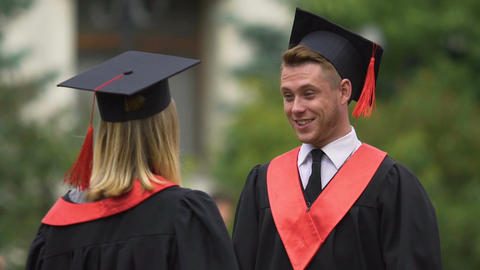 Young people in academic gowns embracing cheerfully, exchanging congratulations Footage