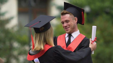 Sincere emotions of cheerful male and female graduates hugging and laughing Footage