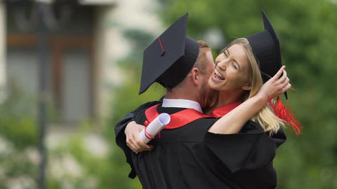 Happy couple of graduates, handsome man embracing and spinning beautiful woman Footage