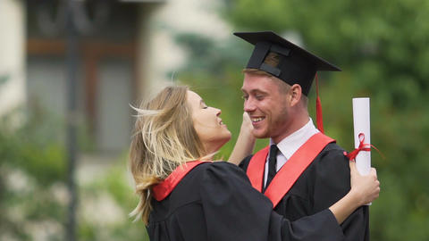 Pretty young woman giving tender kiss to boyfriend, happy couple of graduates Footage