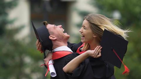 Cheerful couple of graduating students hugging, enjoying happy life together Footage
