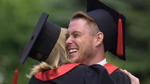 Handsome man smiling sincerely, embracing female friend, graduation ceremony Footage