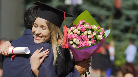 Beautiful female graduate receiving flowers and congratulations from male friend Footage