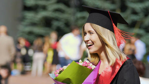 Happy beautiful graduating student holding bunch of flowers, smiling to camera Footage