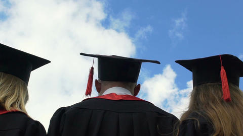 University graduates throwing academic caps up in blue sky, looking into future Footage