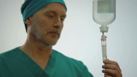 Male physician looking at medicine dropping in IV equipment, doctor nodding Footage