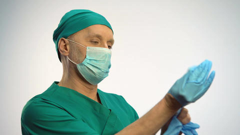 Physician wearing face mask putting on medical gloves, preparing for procedures Footage