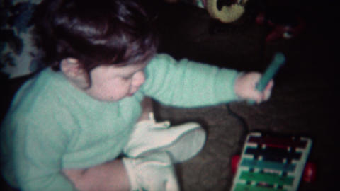 1970: Mom teaches baby how to play colorful xylophone toy Footage