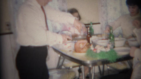 1959: Dad slices holiday ham for family at modest diner table Live Action