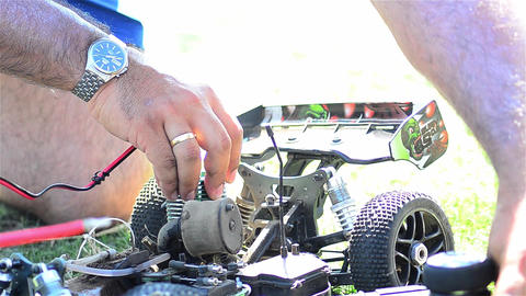 Man prepares a toy car for a speed contest. engine starts 01 Footage