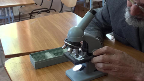 Researcher studying microscopic preparation located on a glass slide 01 Footage