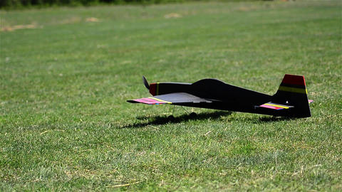 Toy airplane takes off on a pasture with green grass 01 Footage