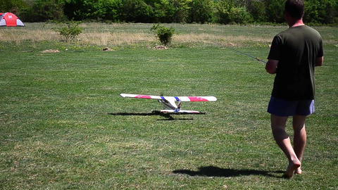 Toy airplane takes off on a pasture with green grass 02 Footage