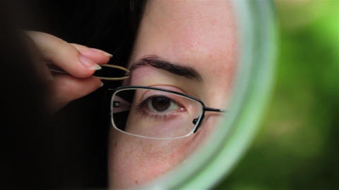 Woman arranges her eyebrows with tweezers in a green frame mirror 01 Live Action