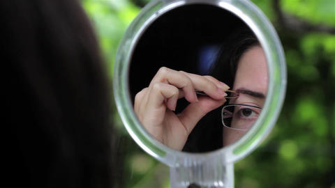 Woman arranges her eyebrows with tweezers in a green frame mirror 03 Live Action