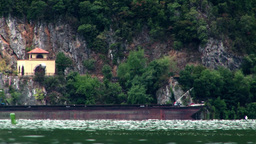 Barges sailing on the Danube near a wooded mountain slope Footage