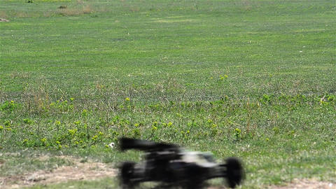 Toy car travels fast on a green grass pasture 2 Footage