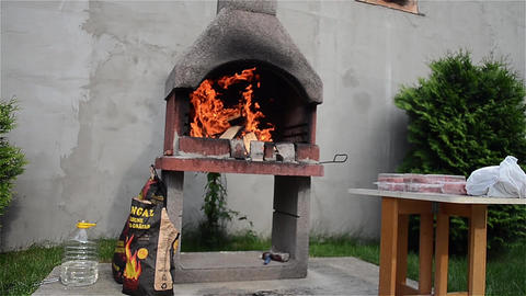 Wood burning, and the fire is big in a barbecue prepared for preparation of food Live Action