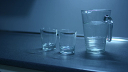 Two glasses and jug filled with water on the kitchen counter Footage
