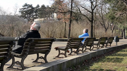 PRAGUE, CZECH REPUBLIC - MARCH 2014: People relax in the park, sits on a bench a Footage