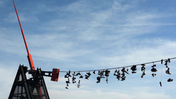 PRAGUE, CZECH REPUBLIC - MARCH 2014: Shoes hanging on a rope with pendulum Footage