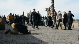 PRAGUE, CZECH REPUBLIC - MARCH 2014: Begging man and people walk around him - on Footage