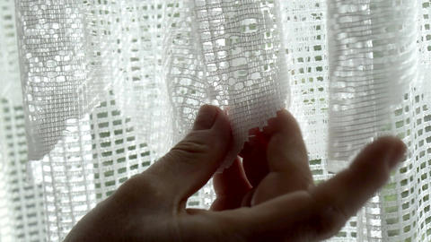 Extreme Closeup of Anonymous Woman Looking at Lace Window Curtains