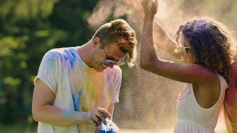 Excited friends throwing colorful powder, laughing and enjoying party together Footage