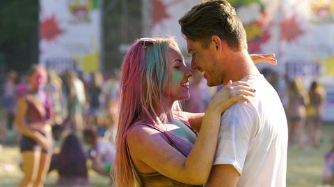 Happy romantic couple hugging and nuzzling, having fun, enjoying color festival Live Action