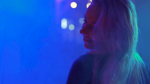 Smiling face of beautiful go-go dancer moving to music in club, smoke and lights Footage
