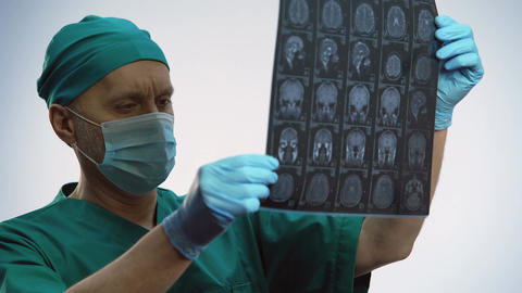 Male physician checking brain scan, treatment results, patient getting better Live Action