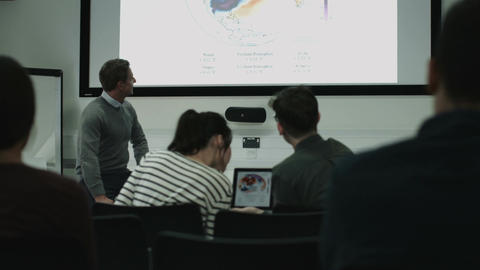 Professor teaching with projector synced to students digital tablets Footage