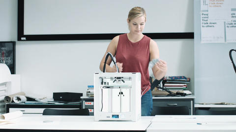 Female designer looking at 3D printed object in design studio Footage