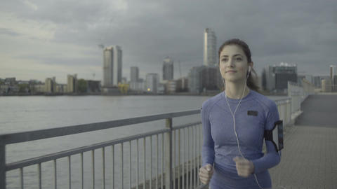 Female runner with headphones jogging by river at sunset Footage