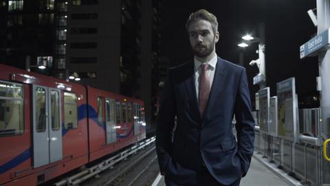 Male business man walking on train platform Footage