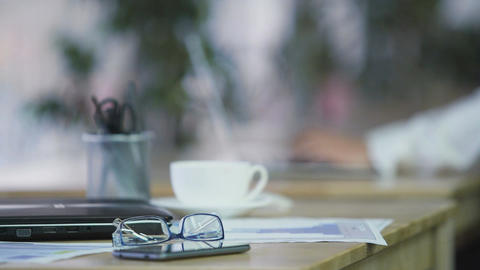 Office work, laptop, smartphone and eyeglasses lying on table. Workplace Footage