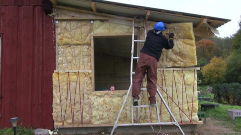 worker with helmet insulating with rock wool wooden house wall Footage