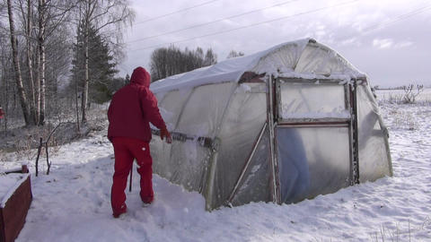 Gardener in red cleaning removing snow from plastic greenhouse Footage