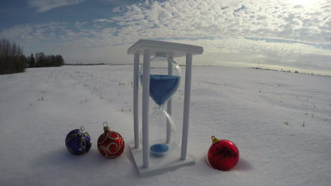 New Year and Christmas time concept. Hourglass sand-glass and Christmas baubles  Footage