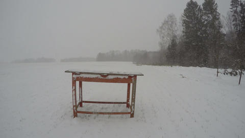 snowstorm snowfall on farm yard and old wooden red table, time lapse 4K Footage