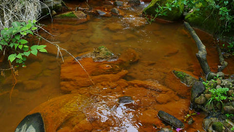 Waste. Old tyre in stream water full of red ferric sediments. Cascades in stream Live Action