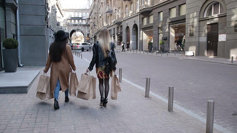 Two happy girlfriends on shopping with bags Filmmaterial
